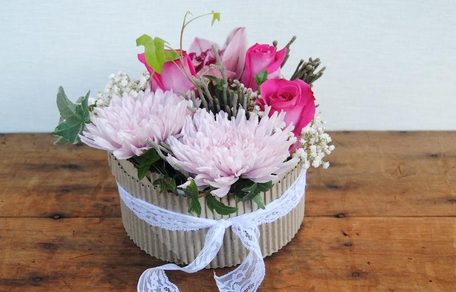 centro rosas y orquídeas en base de cartón