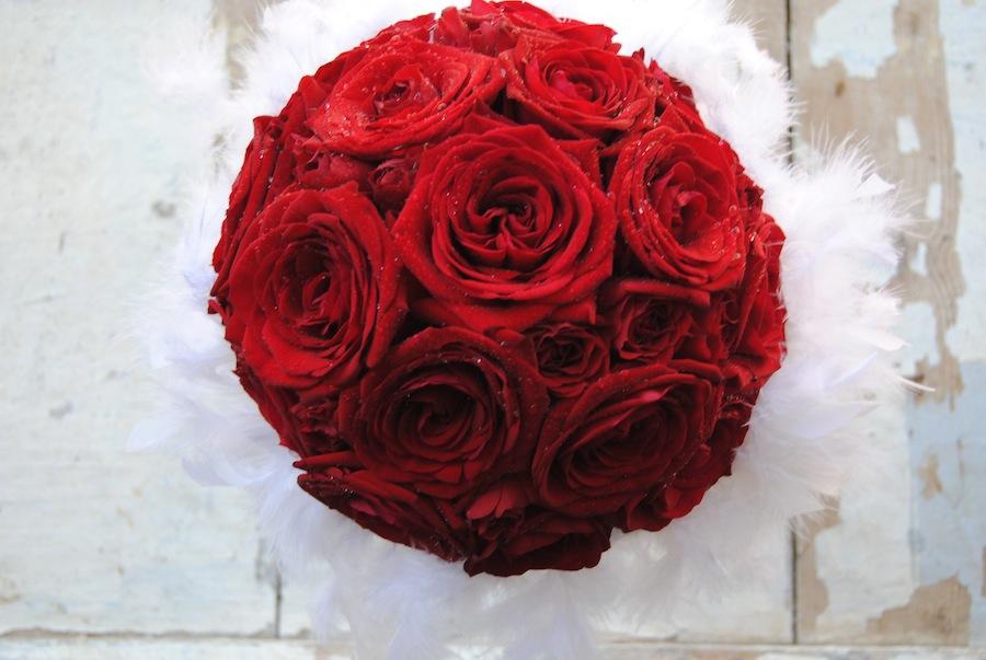 ramo de novia con rosas rojas y pluma blanca