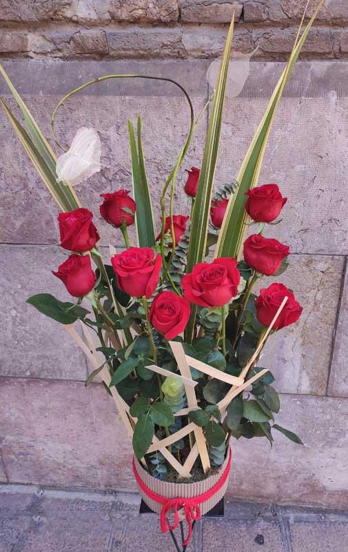 Centro alto con estructura de mimbre y rosas rojas