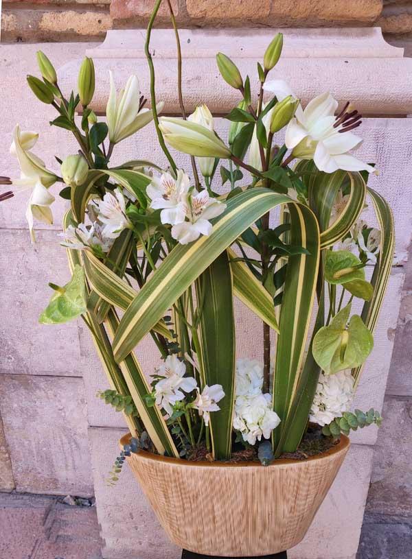 Centro de flores blancas y verdes especiales en una base de cerámica