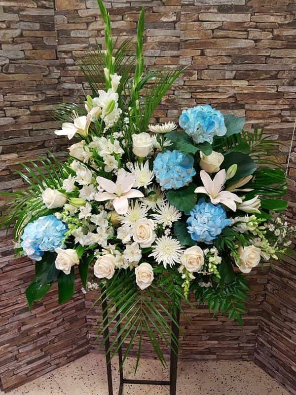 Centro de funeral con flores blancas y hortensias azules
