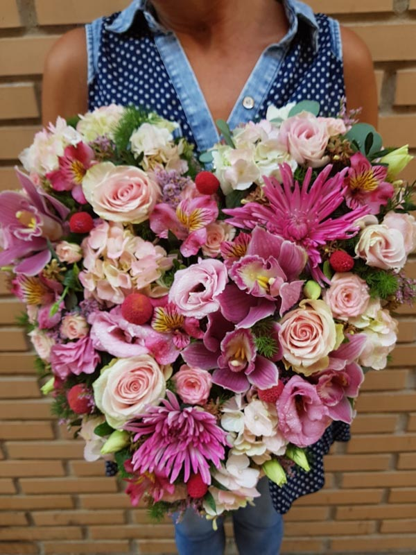 Corazón con flores en distintas flores en color rosa.