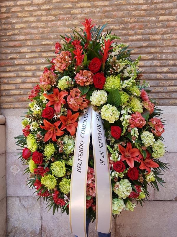 Corona de flores de funeral con plantas en el cabezal