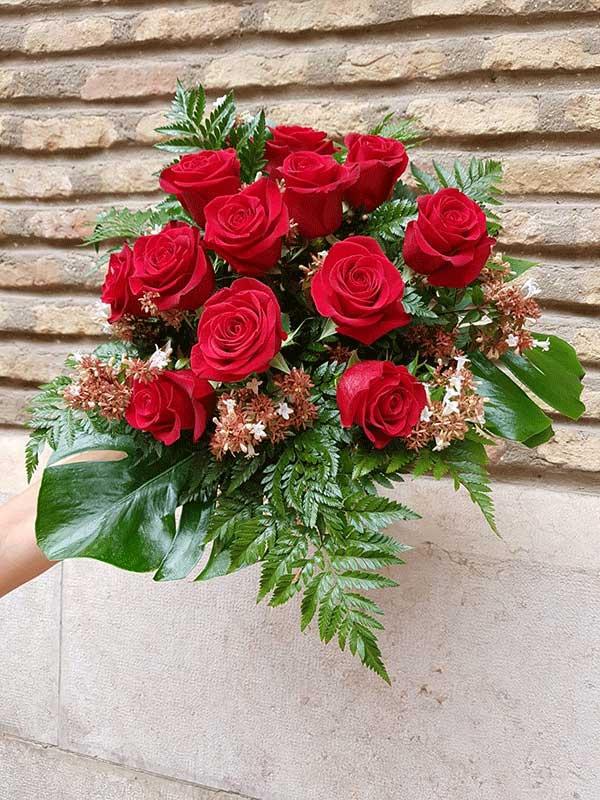 Ramo de 12 rosas rojas delante de una pared de ladrillo